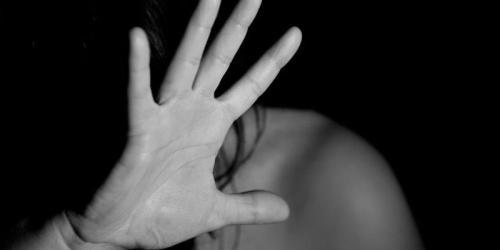 une femme se protégeant de la violence à la main